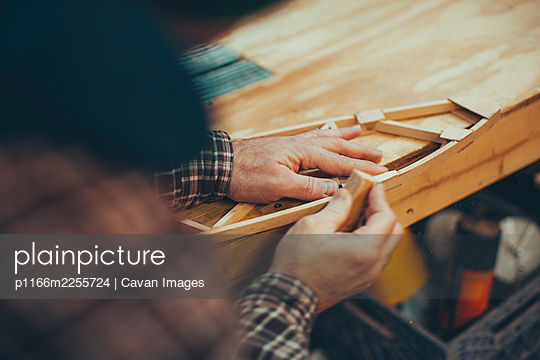 A Caucasian, middle aged man works on a small piece of a wooden airplane in his garage. - p1166m2255724 by Cavan Images