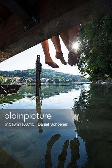 Zwei junge Frauen sitzen auf einem Steg am Rhein, Rheinfelden, Baden-Württemberg, Deutschland - p1316m1160713 von Daniel Schoenen