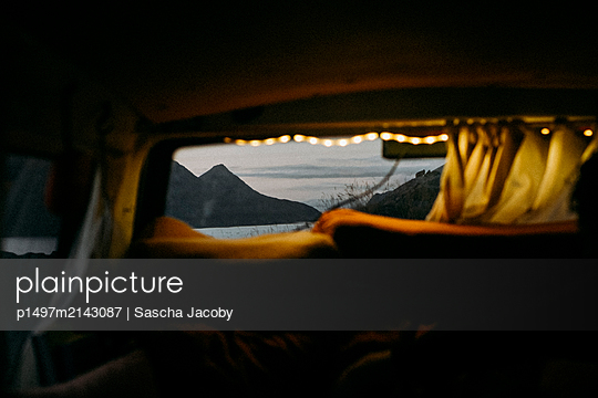 Blick aus Fenster von Campervan mit Lichterkette auf Gebirge in Norwegen im Sonnenuntergang - p1497m2143087 von Sascha Jacoby