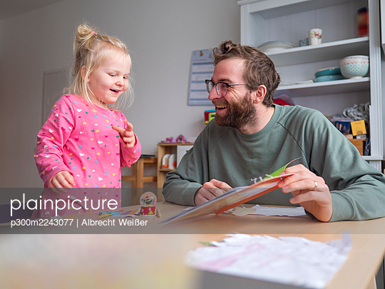Happy father showing book to cute daughter on table at home - p300m2243077 by Albrecht Weißer
