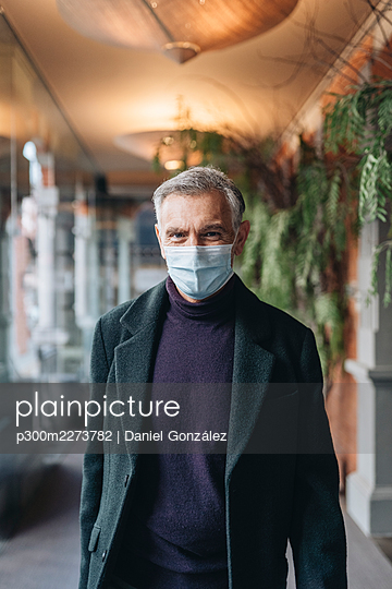 Man in jacket and protective face mask at hotel corridor - p300m2273782 by Daniel González