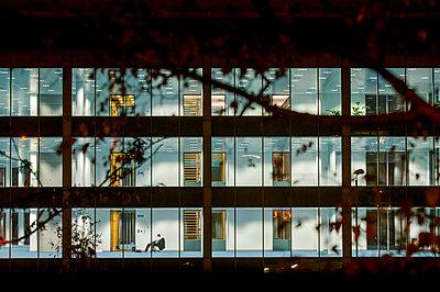 Illuminated office building at night - p1057m2292955 by Stephen Shepherd
