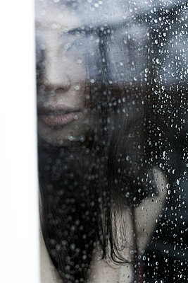 Woman looking out of the window - p1076m957541 by TOBSN