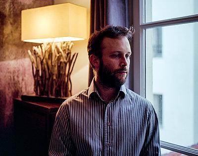 Pensive man by the window - p1118m1539781 by Tarik Yaici
