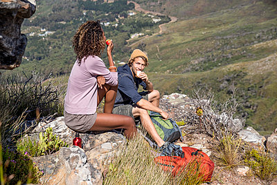 Young hiking couple takes a break in the mountains - p1355m1574192 by Tomasrodriguez