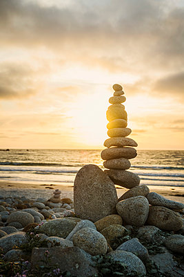 Stacked stones on beach at sunset - p1427m2146621 by Erik Isakson