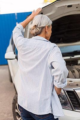 Back view of senior woman looking at car engine - p300m2059431 by Vladimir Godnik
