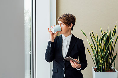 Thoughtful female entrepreneur holding digital tablet while having coffee in office - p300m2276139 by Eugenio Marongiu