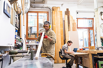 Mature male carpenter working on wood while coworker writing in workshop - p300m2294037 by Eugenio Marongiu