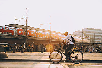 Full length of businessman with backpack riding bicycle on road in city against sky - p426m2169400 by Maskot