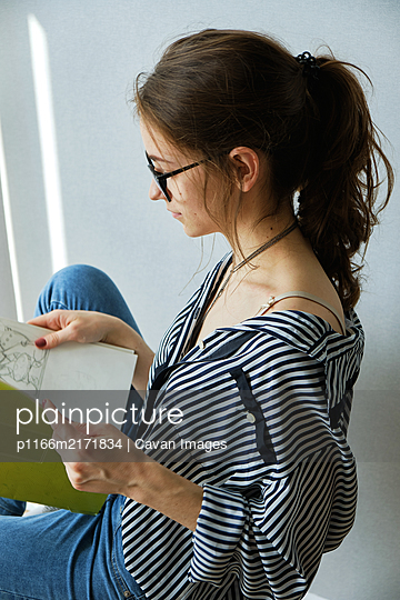 millennial girl draws fabulous images on paper while sitting at home - p1166m2171834 by Cavan Images