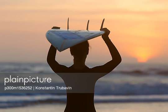 Indonesia, Bali, young woman with surfboard carrying on head at sunset - p300m1536252 by Konstantin Trubavin