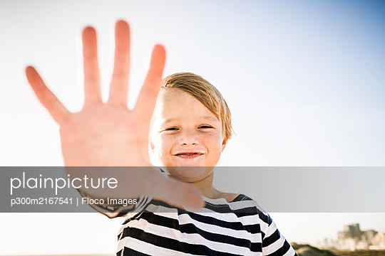 Portrait of smiling boy stretching out his hand - p300m2167541 by Floco Images