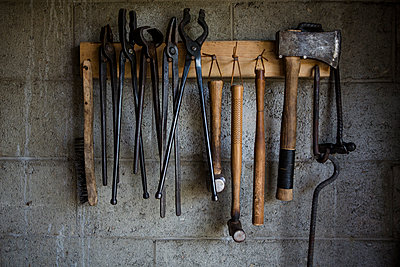 Close-up of work tools hanging on rack at blacksmith shop - p1166m2009243 by Cavan Images
