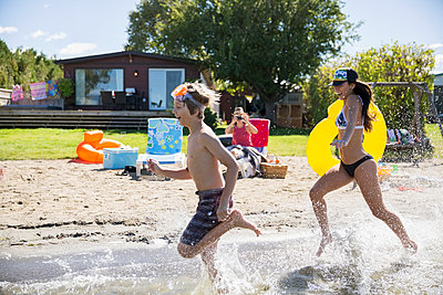 Brother and sister running and splashing in sunny summer lake - p1192m1183784 by Hero Images