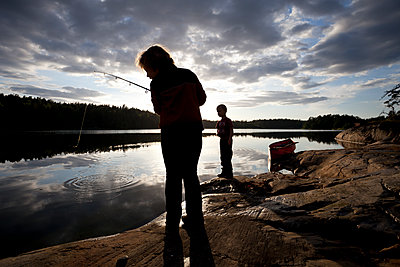 Sweden, Siblings fishing during summer holidays at a lake - p1687m2284287 by Katja Kircher