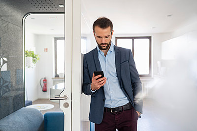 Young entrepreneur using mobile phone while leaning on telephone booth at office - p300m2265296 by Daniel Ingold