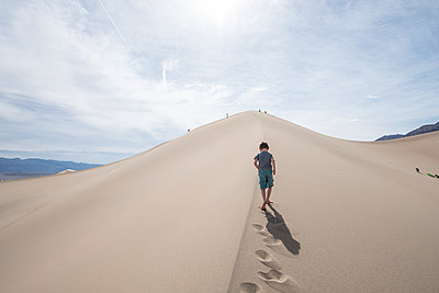Clouds over boy walking on Mesquite Flat Sand Dunes in Death Valley National Park, California, USA - p343m1490639 by Alasdair Turner / Aurora Photos