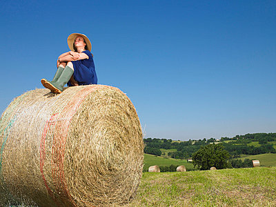 Girl sitting on top of bale of hay - p4293902f by Aurelie and Morgan David De Lossy