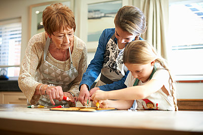 Senior woman and granddaughters decorating Christmas tree cookies - p429m1224286 by Peter Muller