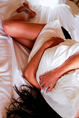Woman clutching pillow on bed - p967m892223 by Wessel Wessels