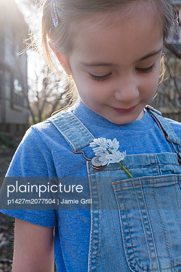 Girl with flower in overalls pocket - p1427m2077504 by Jamie Grill