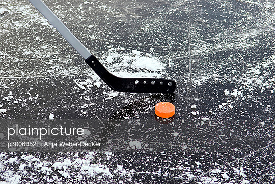 Ice hockey stick and puck on frozen lake, close-up
