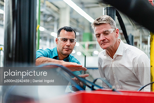 Male professional discussing with colleague while examining machinery equipment in factory - p300m2242459 by Daniel Ingold