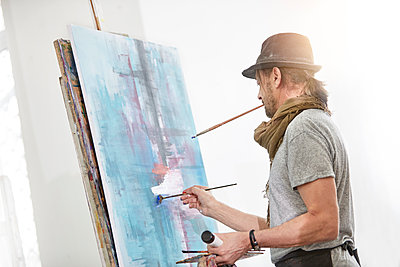 Male artist painting at easel in art studio - p1023m1506495 by Rafal Rodzoch