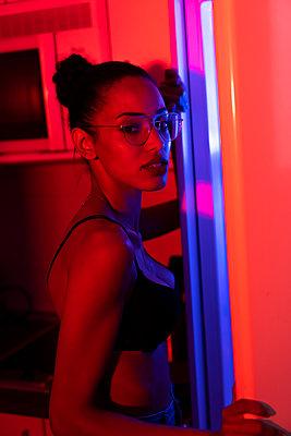 Portrait of beautiful young woman wearing bra and glasses in a dark illuminated room - p300m2012724 by Kike Arnaiz