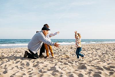 Grandfather playing with his grandchildren on the beach in spring - p300m2103149 von Josep Rovirosa