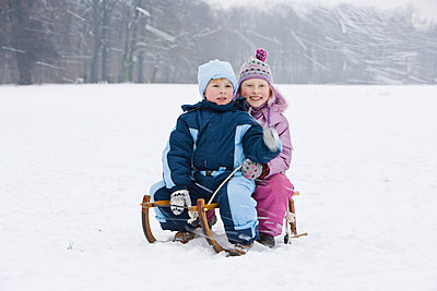 A brother and sister sitting on a sled together tobogganing - p3018761f by Paul Hudson