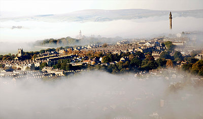 England, West Yorkshire, Halifax. Wainhouse Tower and the town emerging through autumn mist. - p651m2006984 by Robert Birkby