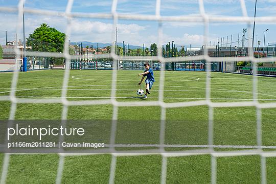 plainpicture - plainpicture p1166m2011281 - Boy kicking soccer ball aga... - plainpicture/Cavan Images