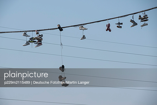 Shoes hanging on rope - p229m2115489 by Martin Langer