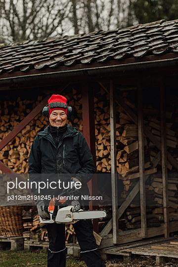 Senior woman holding chainsaw - p312m2191245 by Jennifer Nilsson