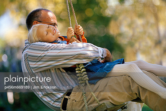 Girl enjoys swinging on tree swing with her father. - p456m669189 by Jim Erickson