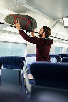 Mann verstaut Gepäck im Zug - p1114m1159728 von Carina Wendland