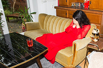 Woman in red dress sits on sofa - p1301m2028142 by Delia Baum