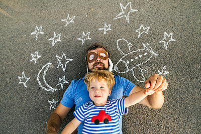 Portrait of mature man wearing pilot hat and his little son lying on asphalt painted with airplane, moon and stars - p300m2060130 by HalfPoint