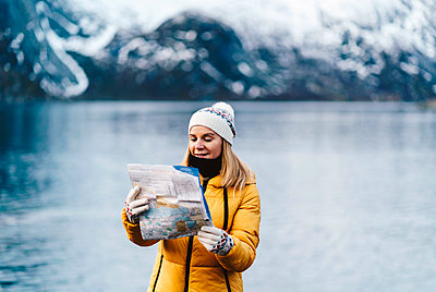 Tourist reading a map at the coast in Hamnoy, Lofoten, Norway - p300m2166334 by Daniel González