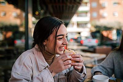 Close-up of cheerful teenage girl eating burger with friend at sidewalk cafe - p300m2251612 by LUPE RODRIGUEZ