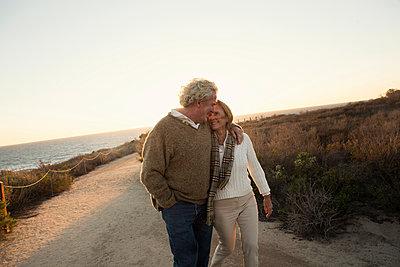 Older Caucasian couple walking on dirt path - p555m1304720 by Kyle Monk