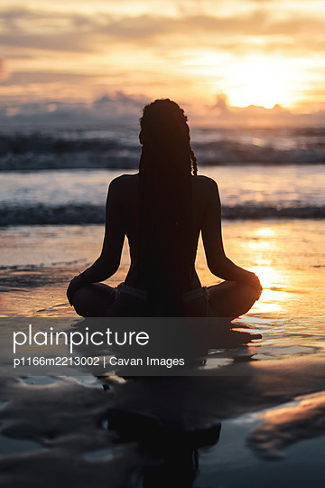 Silhouette of woman doing yoga at sunset - p1166m2213002 by Cavan Images