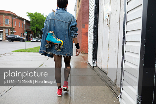 Cool young woman walking on wet sidewalk, carrying roller skates - p1192m2123448 by Hero Images