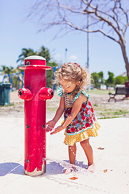 Preschooler girl playing with water at a public playground. - p1166m2246583 by Cavan Images