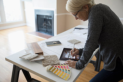 Senior female interior designer planning remodel using digital tablet augmented reality - p1192m1559994 by Hero Images
