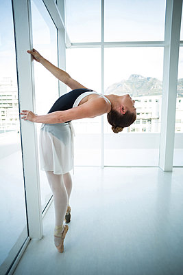 Ballerina practicing ballet dance near window - p1315m1230717 by Wavebreak