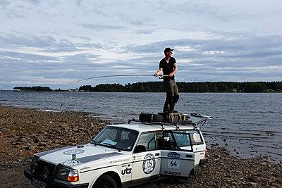 Angler steht auf einem Autodach - p236m1332807 von tranquillium
