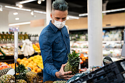 Mid adult man wearing face mask buying pineapple in supermarket - p300m2242273 by VITTA GALLERY